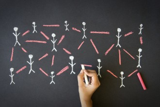 Person drawing a People Network illustration with chalk on a blackboard.